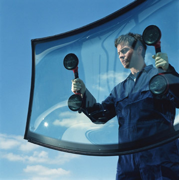 Mechanic carrying car window, view through glass